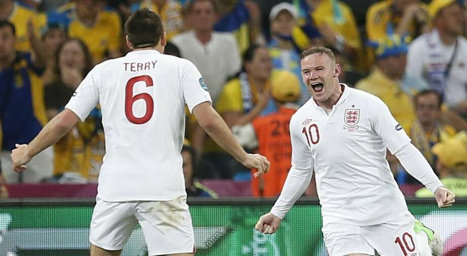 England's Wayne Rooney, right, celebrates after scoring a goal during the Euro 2012 soccer championship Group D match between England and Ukraine in Donetsk, Ukraine, Tuesday, June 19, 2012. (AP Photo/Matthias Schrader) Photo: Matthias Schrader