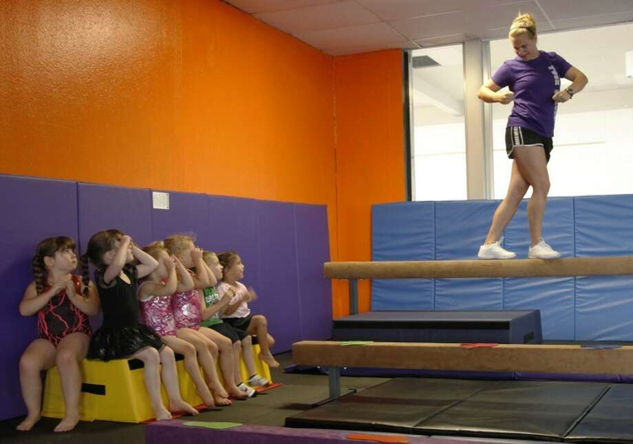 "The preschool class at Tuck & Roll Gymnastics and Cheerleading watch coach and owner Stephanie Rice with their ""gymnastics goggles"" while learning the moves for the June 13 class workout. Chaney Mitchell/Reporter-Telegram Photo: Chaney Mitchell"