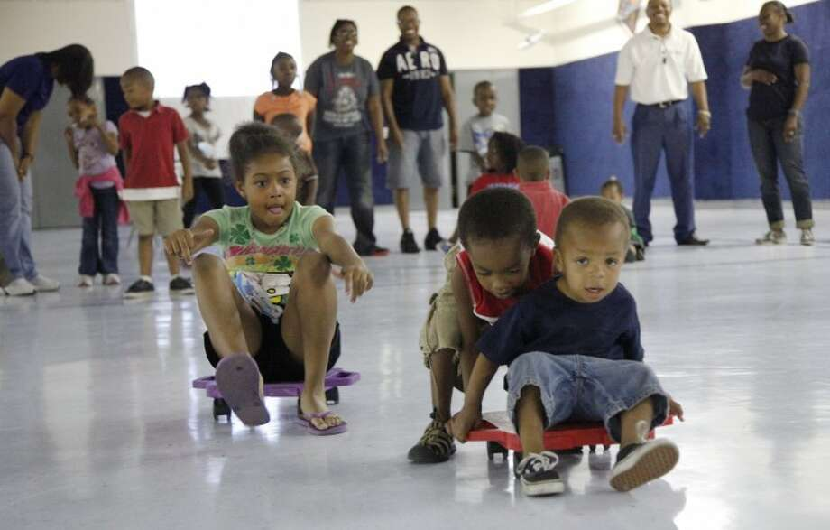 Sanya Green, 8, races Ily'Jah Parker, 3, pushing his little brother Izaiah Parker, 2, during a scooter race June 20 at the Greater Ideal Baptist Church vacation Bible school. Chaney Mitchell/Reporter-Telegram Photo: Chaney Mitchell