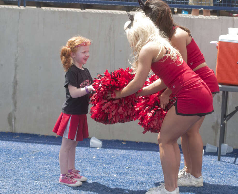 Texas Tech cheerleaders greet a young fan on the sidelines during the Texas Tech spring football practice Saturday at Grande Communications Stadium. James Durbin/Reporter-Telegram Photo: JAMES DURBIN
