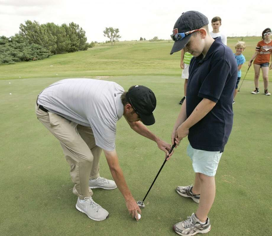 Evan Dunkerson, left, lines Jay Trischitti's, 10, ball with his club face Thursday during the 2012 Junior Golf Summer Program at Hogan Park Golf Course. Cindeka Nealy/Reporter-Telegram Photo: Cindeka Nealy