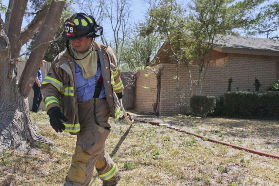 A Midland firefighter pulls back a hose after extinguishing a shed fire Sunday afternoon in the 1000 block of Neely Avenue. Tyler White/Reporter-Telegram Photo: TYLER WHITE
