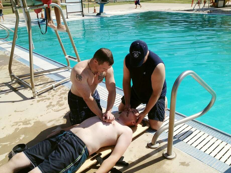Midland firefighters Brian Chatwell works on chest compressions while Omar Hilburn works on ventilations on Arthur Graham during Friday's annual drowning and swift water rescue training with the fire department. Audrie Palmer/Reporter-Telegram Photo: Audrie Palmer