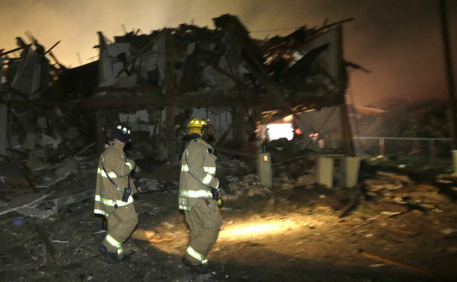 Firefighters walk next to a destroyed apartment complex near a fertilizer plant that exploded earlier in West, Texas, in this photo made early Thursday morning, April 18, 2013. (AP Photo/LM Otero) Photo: LM Otero