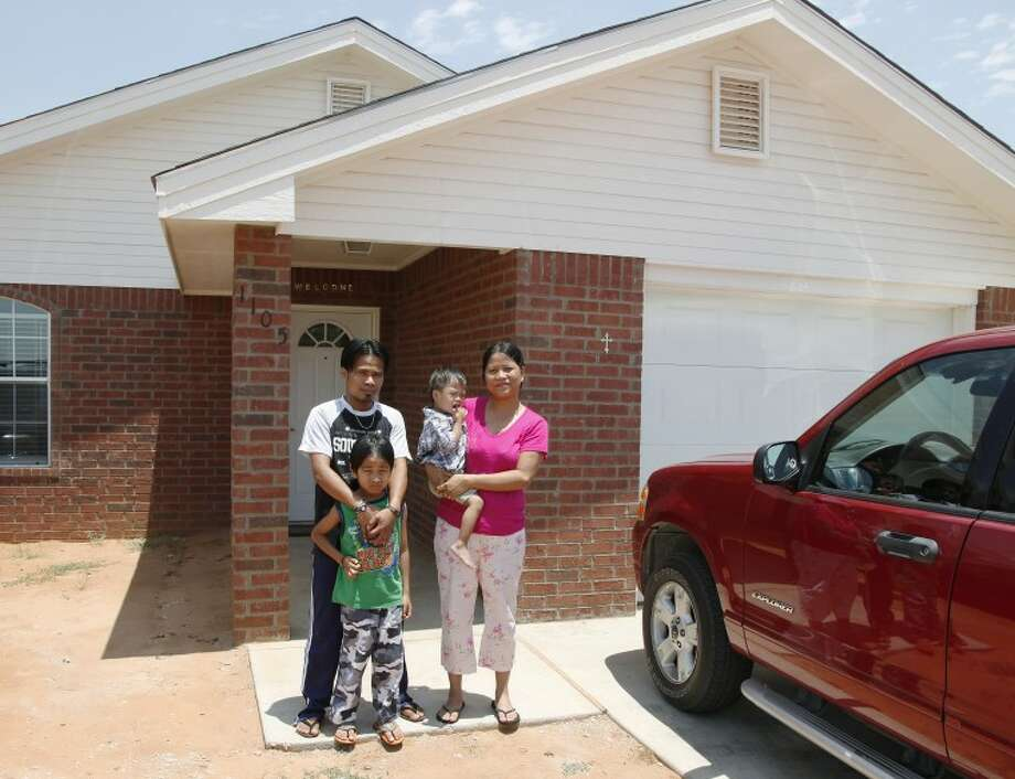 After a year of waiting, Burmese Chin refugees Zung and Biak Thang stand outside their new Midland home June 14, with children Gary, 7, and Livingstone, 3. Chaney Mitchell/Reporter-Telegram Photo: Chaney Mitchell
