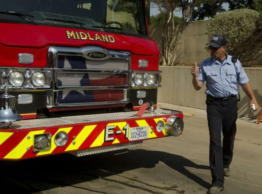 "(FILE PHOTO) Midland firefighter Driver Davis Stacy gives the new engine a thumbs-up after inspecting how community members cleaned it and before it was ""pushed""  into the fire house Saturday during the dedication ceremony to bring it in to service.  Photo: Tim Fischer/Reporter-Telegram"