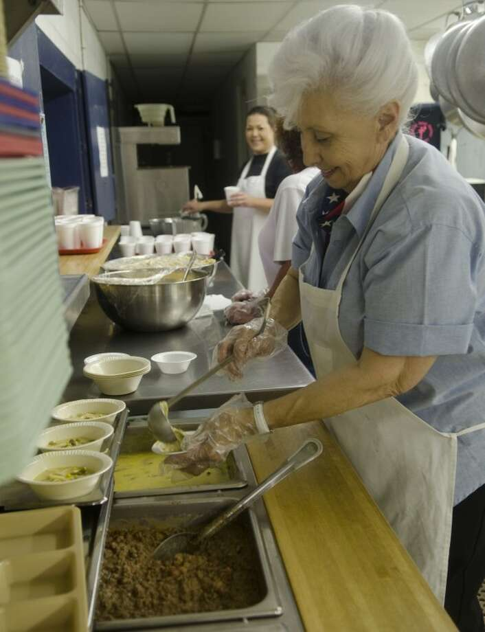 Janis Chapman prepares plates of burritos and soup Monday as she and other volunteers at the Midland Soup Kitchen serve lunch. Photo: Tim Fischer/Reporter-Telegram