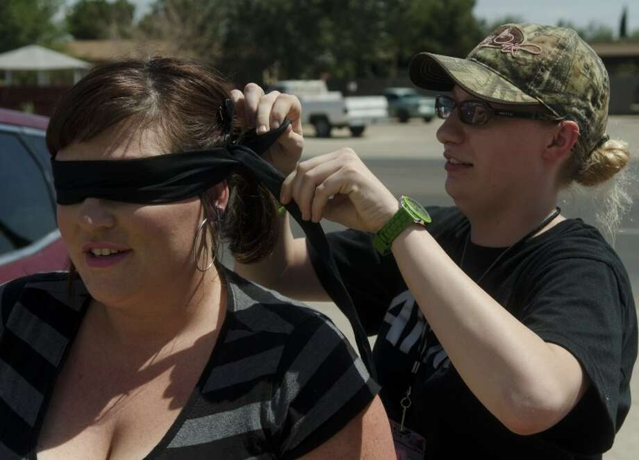 Crystal Buchanan puts a blindfold on medium Kayla Garnett before getting in the car so she has no knowledge of where she is going or what house she will be in during an investigation. Photo by Tim Fischer/Reporter-Telegram Photo: Tim Fischer
