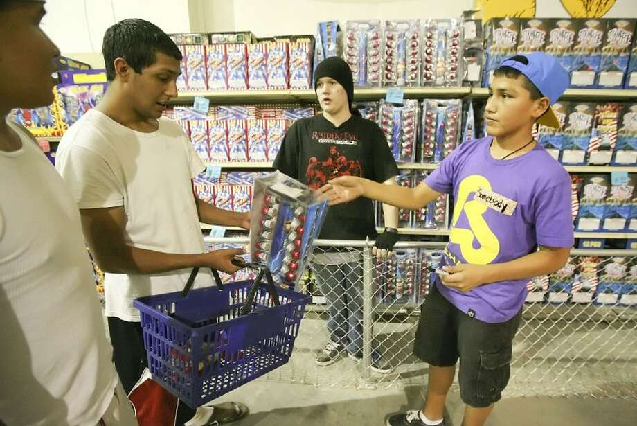 (2012 File Photo) Sean Soukkala, from left, and Jesse Chavez get assistance from Alan Bough, 16, and Tino Madrid, 14, with their fireworks purchases Wednesday at Mr. W Fireworks located on Rankin Highway, south of Interstate 20.  Photo: Cindeka Nealy/Reporter-Telegram