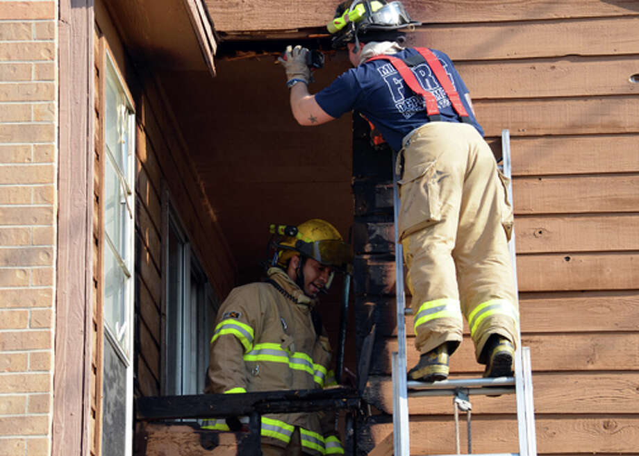 Midland firefighters inspect the damage after extinguishing an apartment balcony fire.