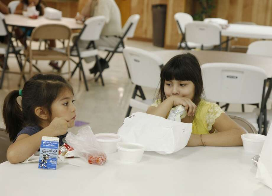 Shelby Bernard, 6, and Isabella Cordova, 7, eat lunch together Wednesday in the otherwise sparce hall at St. Paul United Methodist Church. Chaney Mitchell/reporter-Telegram Photo: Chaney Mitchell