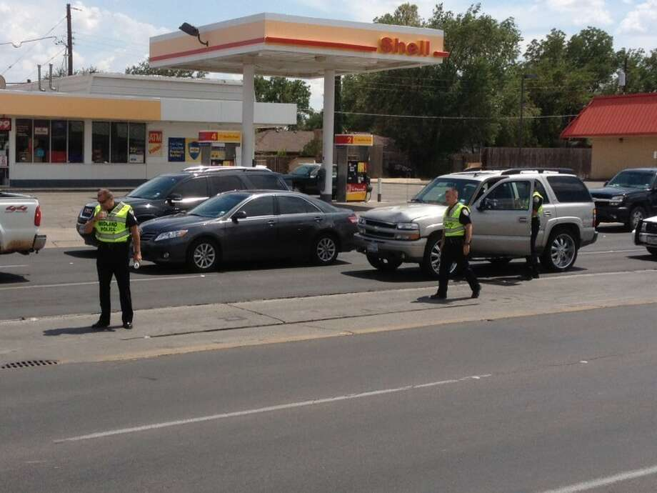 Midland police officers work the scene of a pedestrian vs SUV accident at the intersection of Wadley and Garfield.