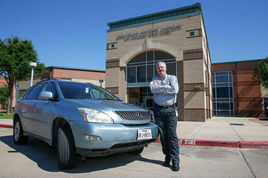 Lance Nauman, director of risk management for Katy Independent School District, stands with his trusty 2009 Lexus, which takes him back and forth to work logging 174 miles daily for his commute.  Photo: Diana L. Porter, Freelance / © Diana L. Porter