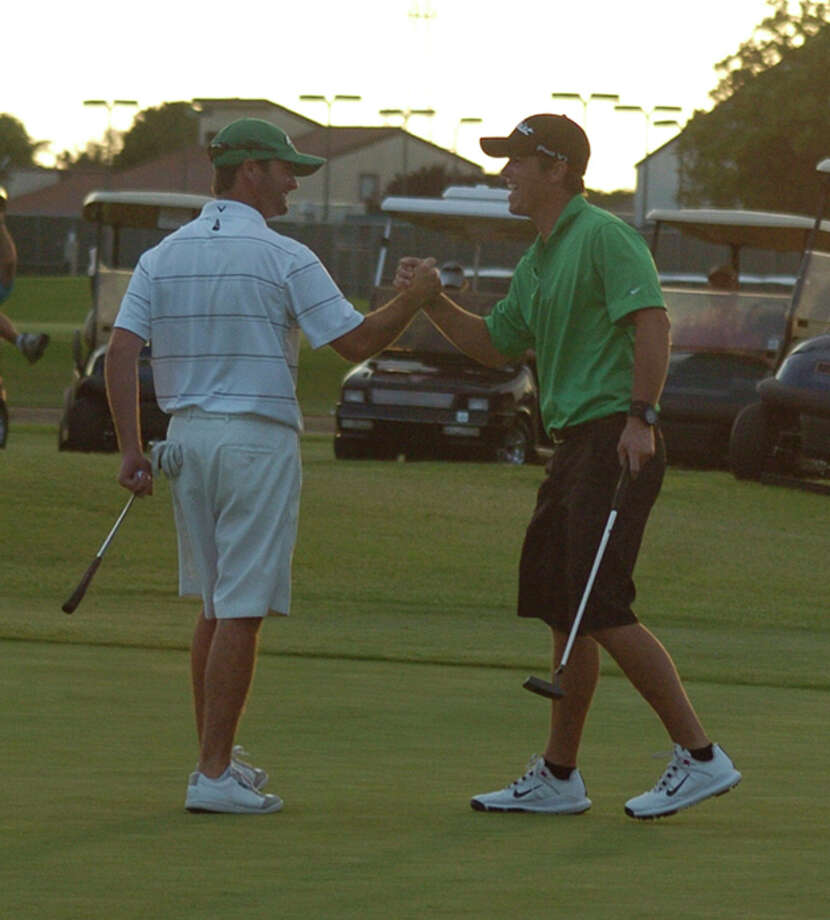 Bobby Whiteside, left, and K.T. Livingston, right, celebrate after Whiteside sank a putt for eagle on the 18th hole of the Jamboree at Green Tree Country Club in 2012. Photo by Len Hayward