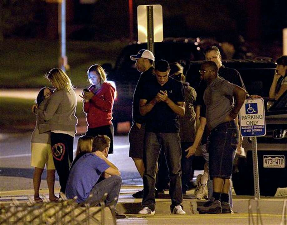 "People use mobile devices as they wait outside Gateway High School where witnesses were brought for questioning after a shooting at a movie theater showing the Batman movie ""The Dark Knight Rises,"" Friday, July 20, 2012 in Aurora, Colo. A gunman wearing a gas mask set off an unknown gas and fired into the crowded movie theater killing 12 people and injuring at least 50 others, authorities said. (AP Photo/Barry Gutierrez) Photo: Barry Gutierrez / AP2012"