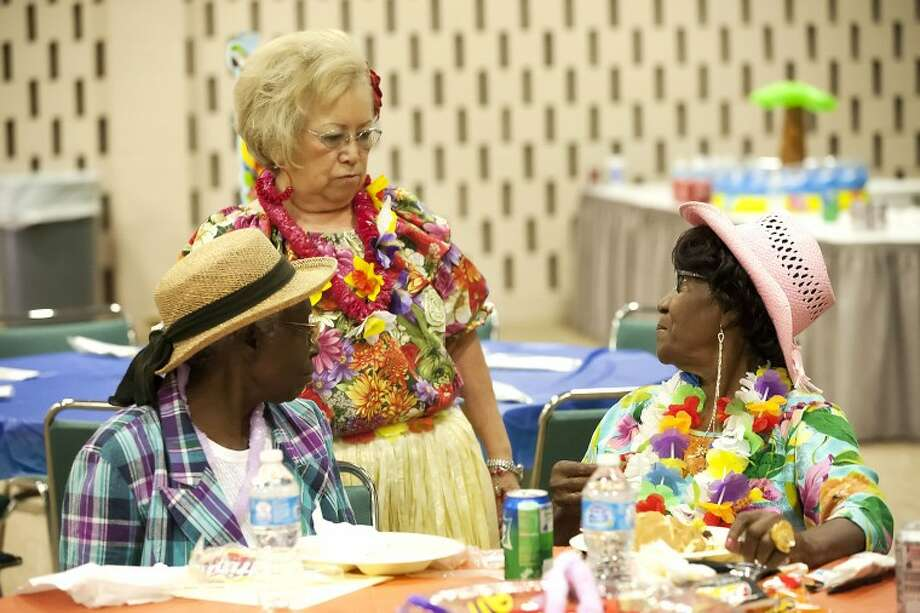 Mable Smith, from left, listens as Hope Barboza talks to Flo Johnson, Thursday during the Community and Senior Services Burger Bash at Midland Center. Senior Corps volunteers were recognized for their 200,000 hours of community service during the event. Cindeka Nealy/Reporter-Telegram Photo: Cindeka Nealy
