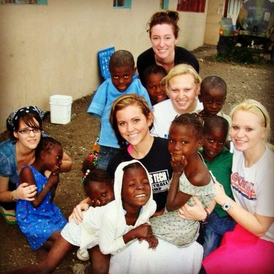 Becca Roepke, center, Katelyn Morphew and Amanda Morphew play with children at an orphanage in Haiti. Photo: Courtesy Photo