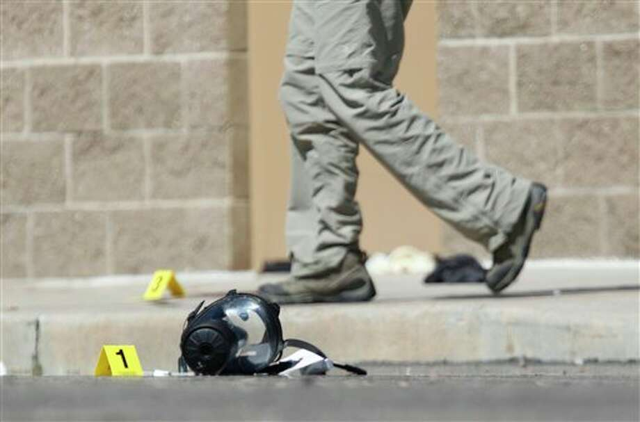 Yellow markers sit next to evidence, including a gas mask, as police investigate the scene outside the Century 16 movie theater east of the Aurora Mall in Aurora, Colo. on Friday, July 20, 2012. A gunman in a gas mask barged into a crowded Denver-area theater during a midnight showing of the Batman movie on Friday, hurled a gas canister and then opened fire in one of the deadliest mass shootings in recent U.S. history. (AP Photo/David Zalubowski) Photo: David Zalubowski / 2012 AP
