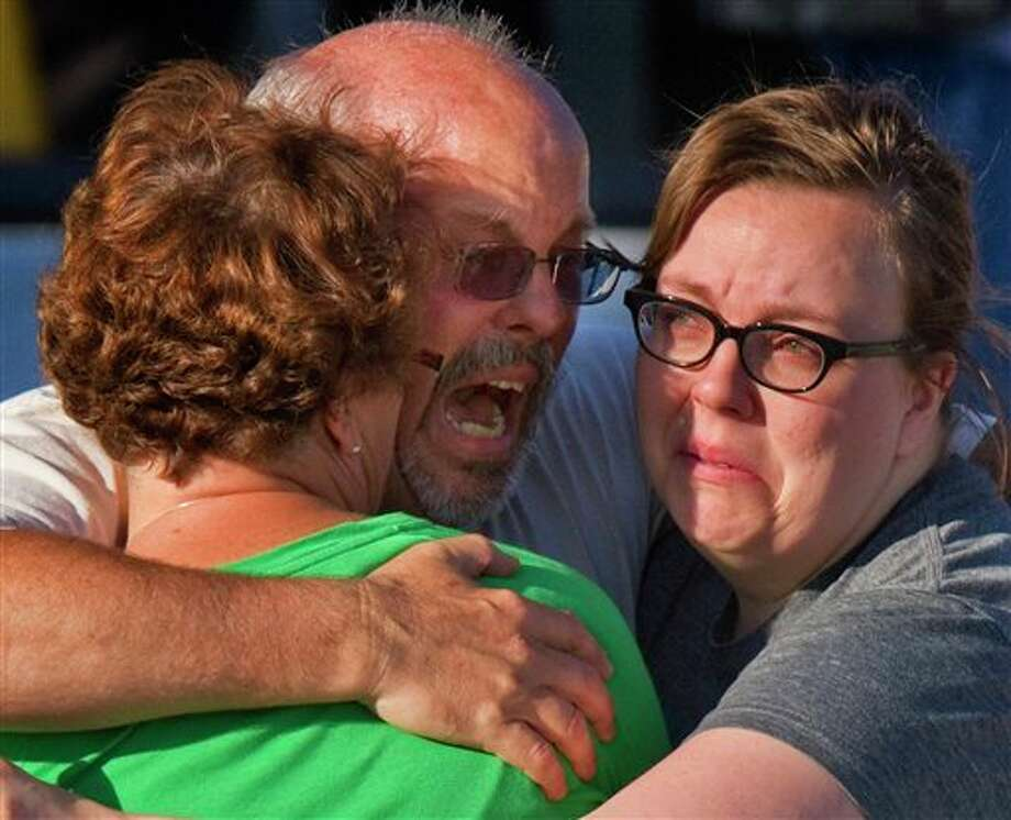 "Tom Sullivan, center, embraces family members outside Gateway High School where he has been searching franticly for his son Alex Sullivan who celebrated his 27th birthday by going to see ""The Dark Knight Rises,"" movie where a gunman opened fire Friday, July 20, 2012, in Aurora, Colo. (AP Photo/Barry Gutierrez) Photo: Barry Gutierrez / 2012 AP"