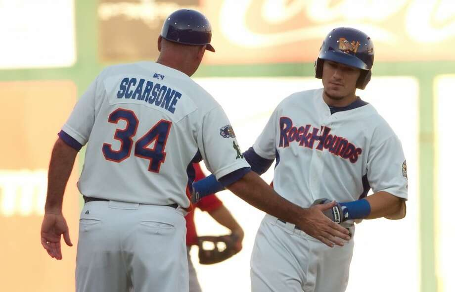 Midland RockHounds manager Steve Scarsone gives five to left fielder Adam Heether after he hit a homerun during the fourth inning of the Hounds game against the Frisco RoughRiders at Citibank Ballpark. Cindeka Nealy/Reporter-Telegram Photo: Cindeka Nealy