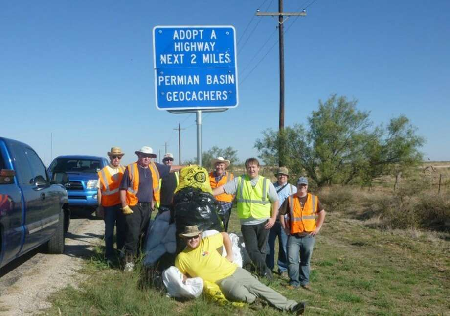 Members of the Permian Basin Cachers Association stand near the Adopt-a-Highway sign after cleaning an area of Highway 349 in October. Photo: Courtesy Photo