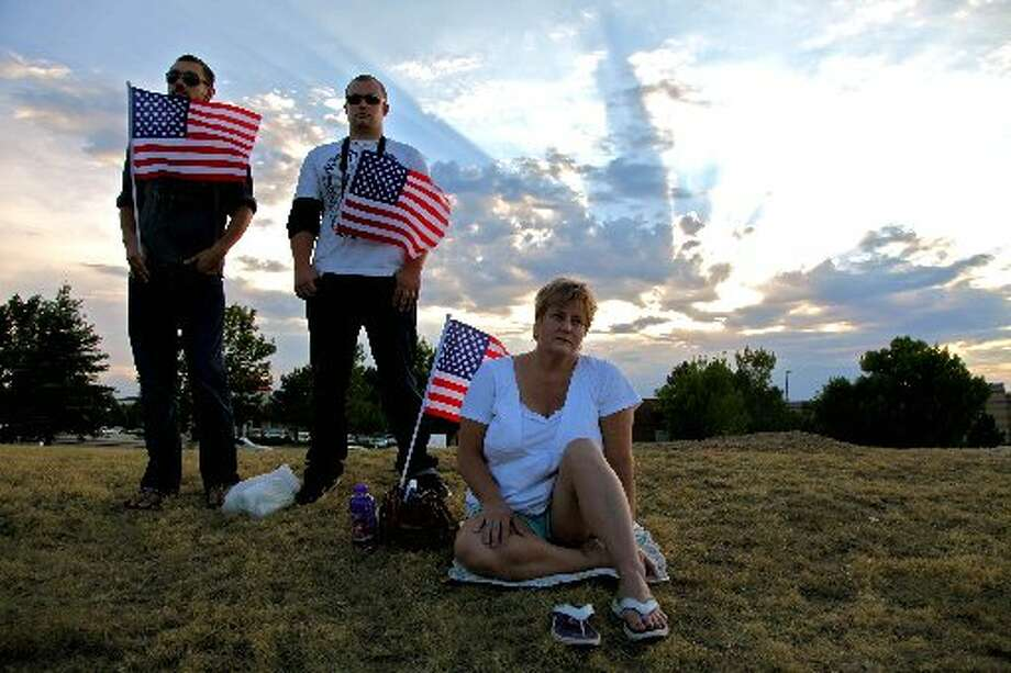 """People hold American flags at a vigil Friday night in Aurora, Colo. Authorities report that 12 people died and at least 70 people were injured during an assault at a theater during a midnight premiere of """"The Dark Knight."""" Photo: Associated Press"""