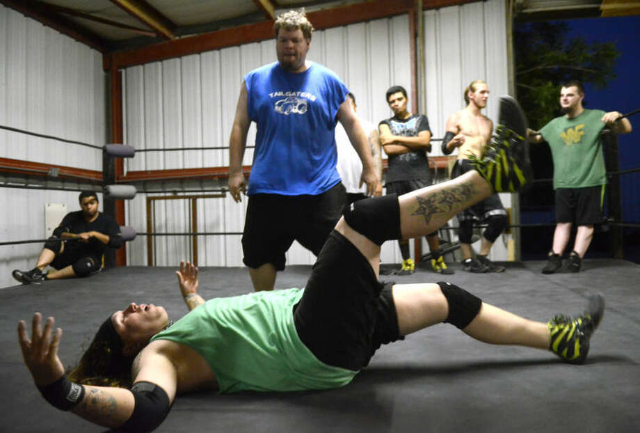 "MRT sports reporter Jonathan Hull (blue shirt) reacts after taking down ""Rockstar"" Dextor King with a shoulder tackle Tuesday at the Old School Wrestling facility in Odessa. James Durbin/Reporter-Telegram Photo: JAMES DURBIN"