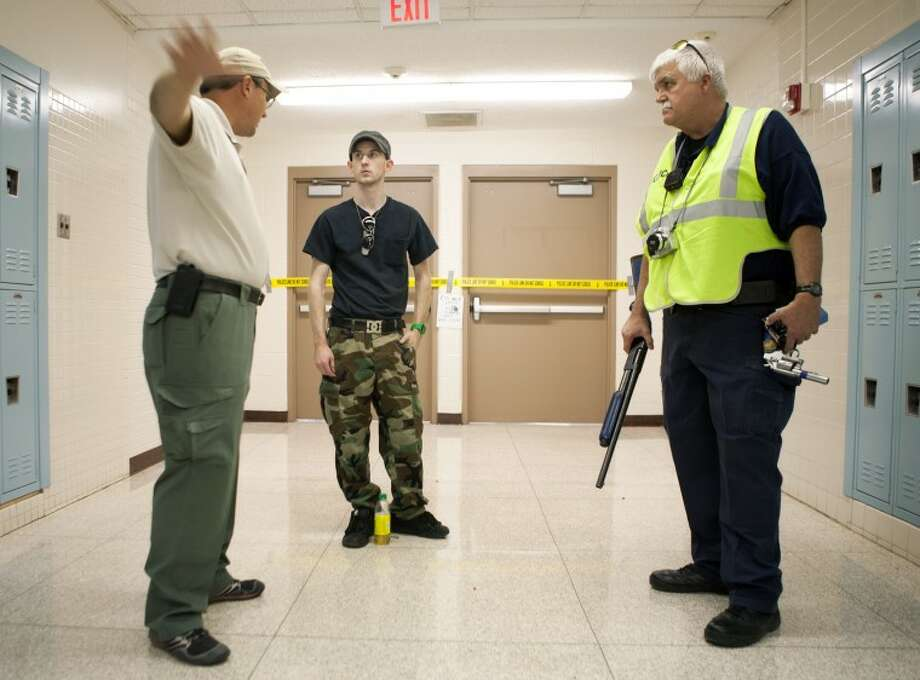 (File Photo) Midland Police Sgt. Brian Rackow, from left, Nicholas Colburn and Midland ISD Lt. Mike Bowen, a exercise safety officer, discuss Colburn's role as the shooter Thursday before the start of an active shooter exercise at Midland Freshman High School. Photo: Cindeka Nealy/Reporter-Telegram