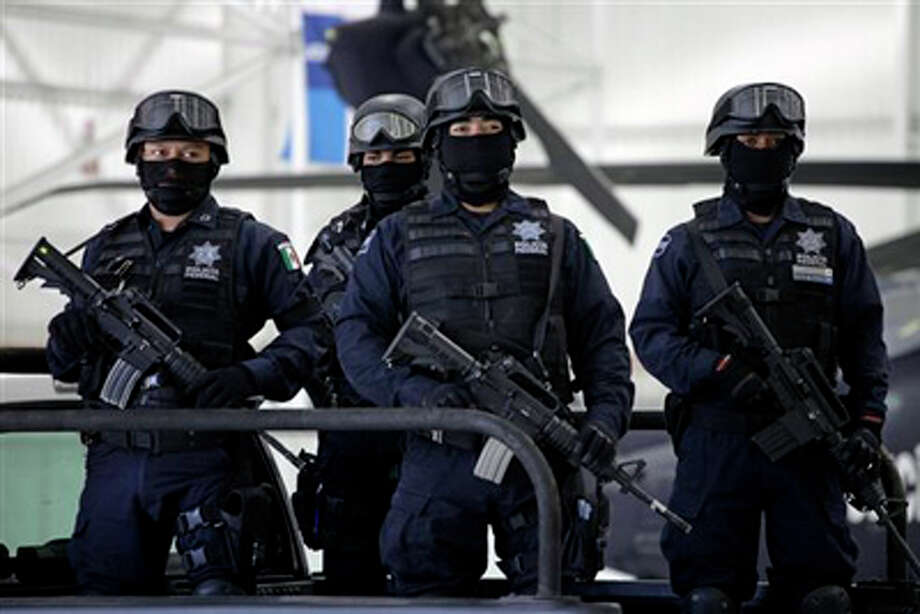 "(File Photo) Federal police officers stand on guard during the presentation to the press of suspect Edgar Huerta Montiel, 22, aka ""El Wache"", an alleged member of the Mexican Zetas drug cartel in Mexico City, Friday, June 17, 2011. According to police, Huerta was arrested Thursday during an operation in the Mexican state of Zacatecas. Photo: Eduardo Verdugo/AP / AP"