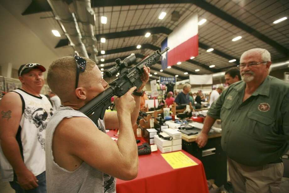 Daniel Scott, from left, gets a feel and looks through the scope of Stay Safe owner and retired police Sgt. Michial Dunlap's factory built Sabre M-4 rifle, Saturday during the Silver Spur Gun & Knife Show at the Midland County Horseshoe. Cindeka Nealy/Reporter-Telegram Photo: Cindeka Nealy