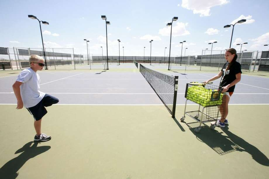 Matt Hall, 12, left, stretches while instructor Charlotte Dawson waits to begin his lesson Wednesday at the Bush Tennis Center. Cindeka Nealy/Reporter-Telegram Photo: Cindeka Nealy