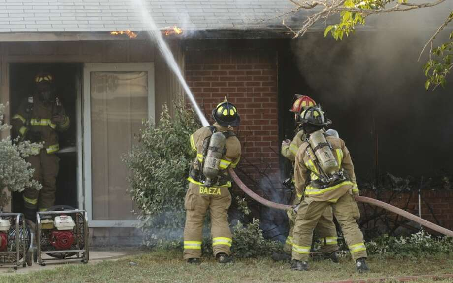 Midland firefighters control a fire in a home at 1417 E. Chestnut Tuesday evening. No one was injured in the blaze. Photo by Tim Fischer\ Reporter-Telegram Photo: Tim Fischer