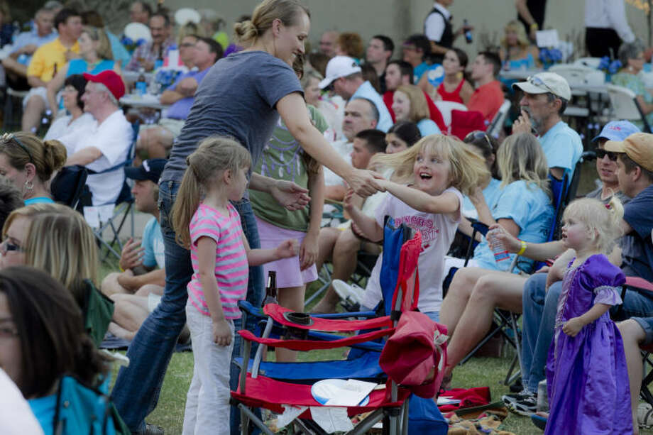 """Tonya Davis dances with 5-year-old Abby during a free concert by the Elton John tribute band """"Bennie and the Jets"""" to benefit the Aphasia Center of West Texas on Friday at Centennial Plaza. James Durbin/Reporter-Telegram Photo: JAMES DURBIN"""