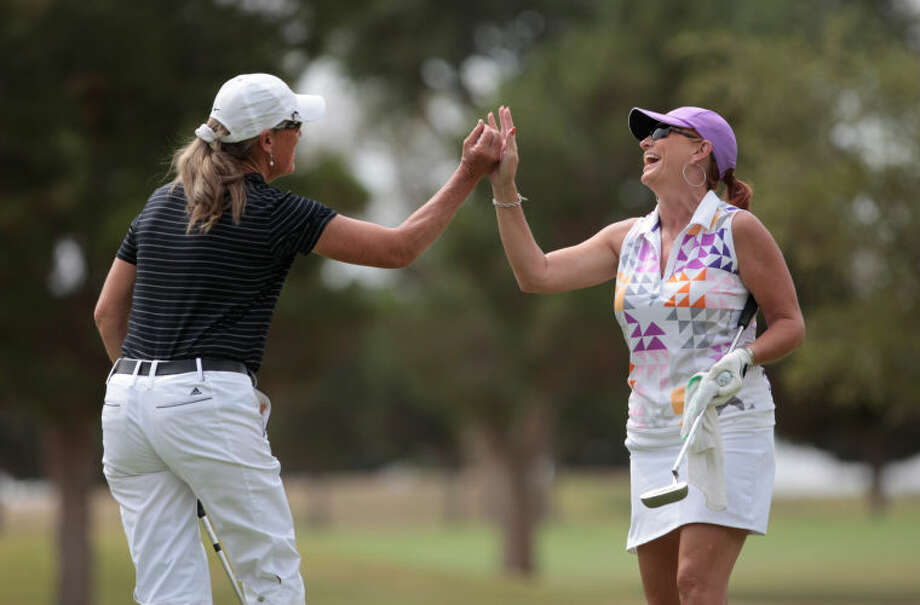 Marian Barker, left, gets a high-five from Lacy Gasser after sinking a birdie putt on the 9th green of the Odessa Country Club on Friday during the Women's West Texas Golf Association Championship. Photo: Ryan Evon|Odessa American