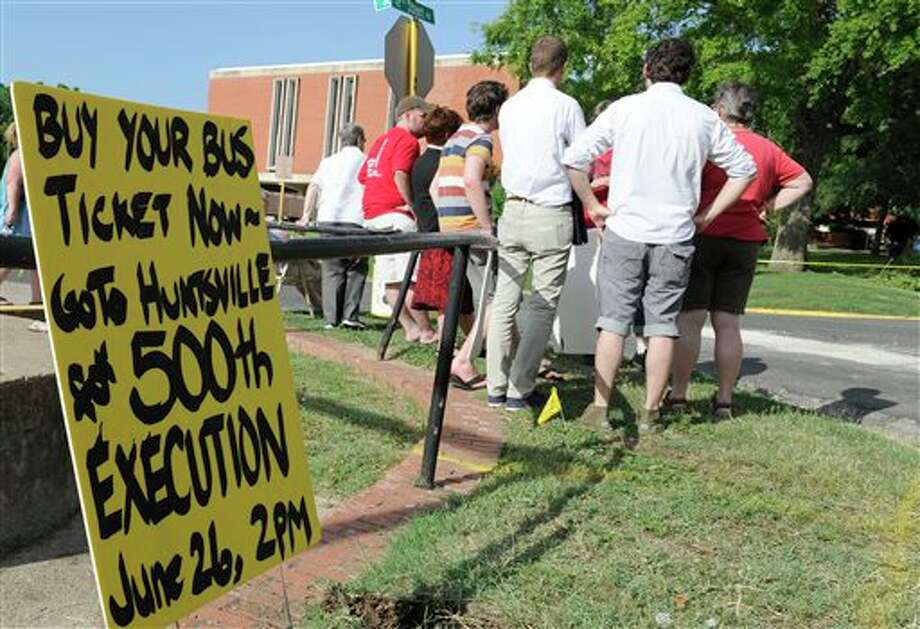 In this photo taken June 12, 2013, death penalty opponents gather outside the Huntsville Unit before the execution of confessed killer Elroy Chester in Huntsville, Texas. Chester, convicted of the 1988 the fatal shooting of Port Arthur firefighter Willie Ryman III, was the 499th prisoner to be executed in Texas since 1982. (AP Photo/Pat Sullivan) Photo: Pat Sullivan / AP