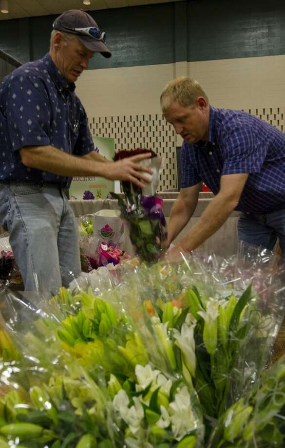 Dan Logsdon, left and Hein Verver remove wrappers as they get ready to set their displays Friday evening for the West Texas-New Mexico Florist Association convention today at  Midland Center. Photo: Tim Fischer/Reporter-Telegram