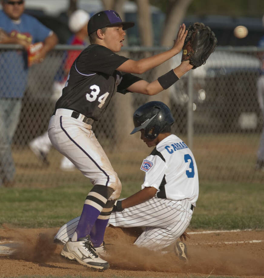 Eastern's Shawn Carrassco safely slides into third for a triple as Mid City's Riggs McDonald reaches for the ball Monday at Butler Park. Tim Fischer\Reporter-Telegram Photo: Tim Fischer