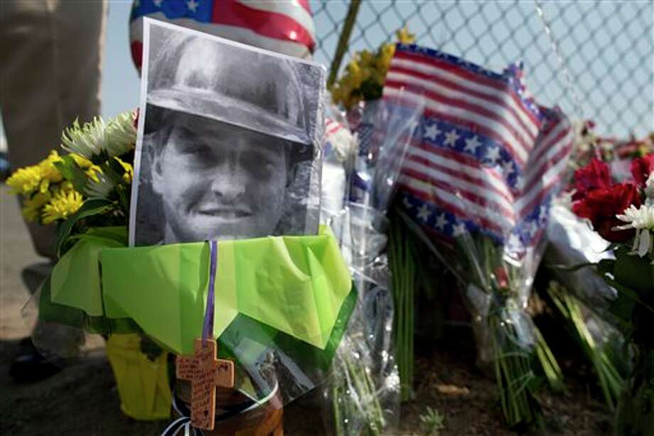 A photo of one of the 19 Granite Mountain Hot Shot crew members who was killed fighting a wild land fire near Yarnell, Ariz. on Sunday, sits at a makeshift memorial outside the crew's fire station, Monday, July 1, 2013 in Prescott, Ariz. An out-of-control blaze overtook the elite group of firefighters trained to battle the fiercest wildfires, killing 19 members as they tried to protect themselves from the flames under fire-resistant shields. The disaster Sunday afternoon all but wiped out the 20-member Hotshot fire crew leaving the city's fire department reeling. (AP Photo/Julie Jacobson) Photo: Julie Jacobson / AP