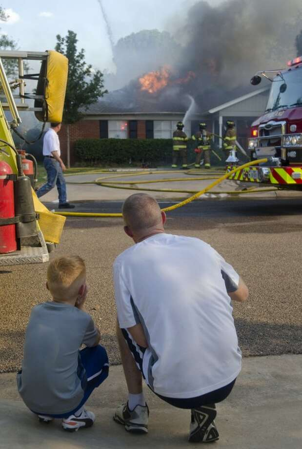 Off-duty Midland firefighter, Michael Tully, points out techniques to his son, Caden, 6, Monday afternoon at a fire on Terrace, down the street from their home. Photo by Tim Fischer\ Reporter-Telegram Photo: Tim Fischer