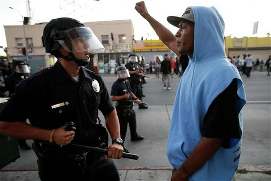 A protester confronts a Los Angles police officer during a demonstration in reaction to the acquittal of neighborhood watch volunteer George Zimmerman on Monday, July 15, 2013, in Los Angeles. Anger over the acquittal of a U.S. neighborhood watch volunteer who shot dead an unarmed black teenager continued Monday, with civil rights leaders saying mostly peaceful protests will continue this weekend with vigils in dozens of cities. (AP Photo/Jae C. Hong) Photo: Jae C. Hong / AP
