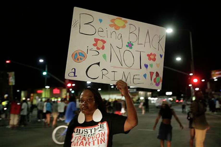 A woman holds up a sign during a demonstration in reaction to the acquittal of neighborhood watch volunteer George Zimmerman on Monday, July 15, 2013, in Los Angeles. Anger over the acquittal of a U.S. neighborhood watch volunteer who shot dead an unarmed black teenager continued Monday, with civil rights leaders saying mostly peaceful protests will continue this weekend with vigils in dozens of cities. (AP Photo/Jae C. Hong) Photo: Jae C. Hong / AP