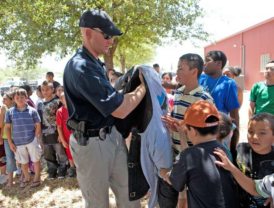 Taylor Welch walks around to let MPD Kids Police Academy participants feel the bite suit that Officer Jimmy Young wears during the demonstration Wednesday at Casa De Amigos. Cindeka Nealy/Reporter-Telegram Photo: Cindeka Nealy