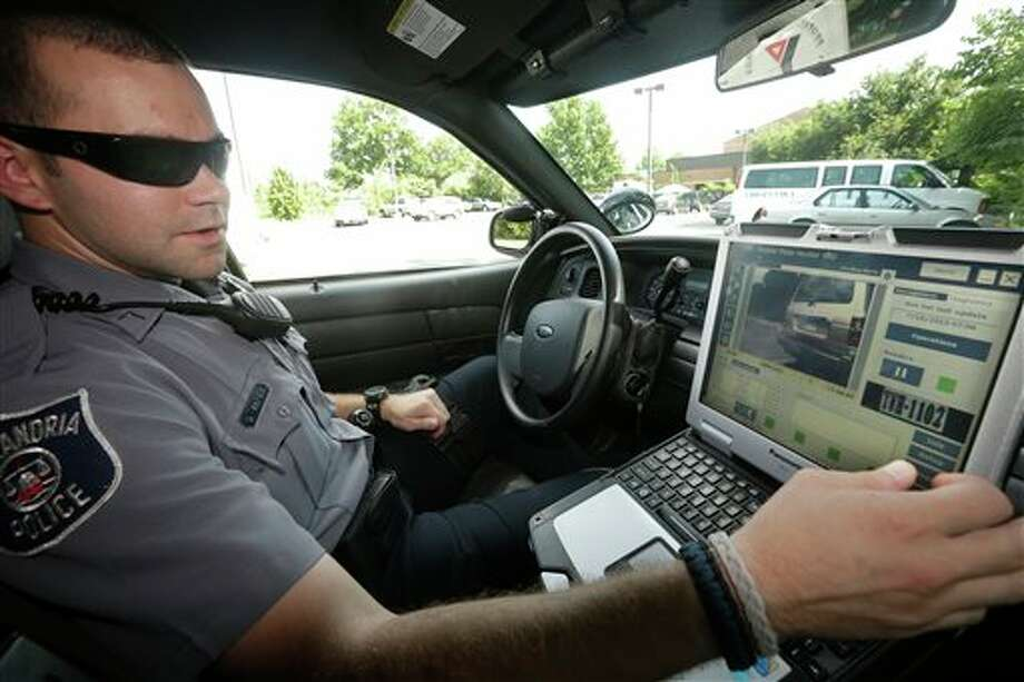 Officer Dennis Vafier, of the Alexandria Police Department, uses a laptop in his squad car to scan vehicle license plates during his patrols, Tuesday, July 16, 2013, in Alexandria, Va. Local police departments across the country have amassed millions of digital records on the location and movements of vehicles with a license plate using automated scanners. Affixed to police cars, bridges or buildings, the scanners capture images of passing or parked vehicles and note their location, dumping that information into police databases. Departments keep the records for weeks or even years. (AP Photo/Pablo Martinez Monsivais) Photo: Pablo Martinez Monsivais / AP