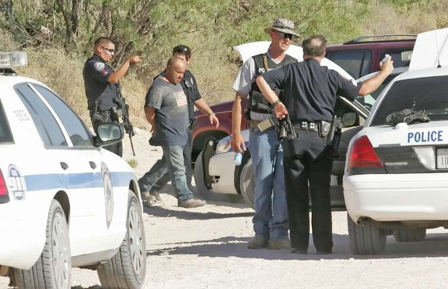 Midland police officers escort Francisco Lozano Baeza to an awaiting patrol car after he was tracked down by an MPD K-9 Friday evening in a field located a half of a mile south of East County Road 160, on CR 1130. Photo: Cindeka Nealy/Reporter-Telegram