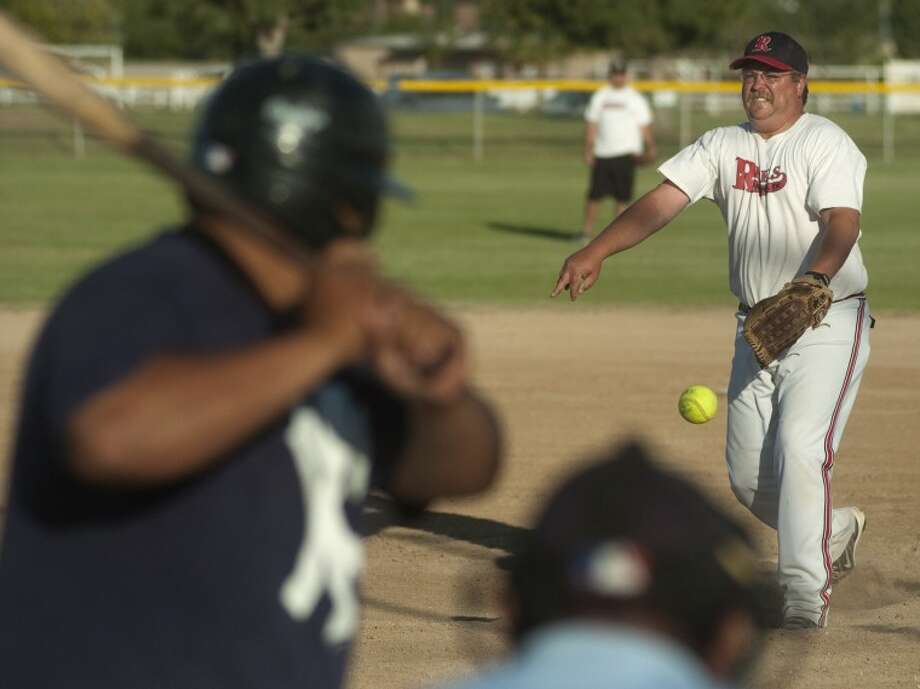 Dave Parker with the Rebels, delivers a pitch to Virgil Mancha with the Angels Wednesday evening at a mens fastpitch softball game. Photo by Tim Fischer/Midland Reporter-Telegram Photo: Tim Fischer