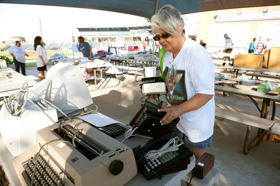 Linda Rodriguez takes a look at some the electronic devices on sale Saturday morning during the RockHounds and Citibank garage sale to benefit the March of Dimes at Citibank Ballpark. Cindeka Nealy/Reporter-Telegram Photo: Cindeka Nealy