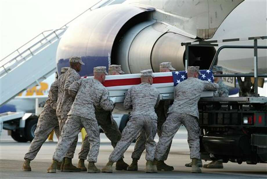 A Marine carry team carries transfer cases containing the remains of Marine Pfc. Josue Ibarra of Midland, Texas, upon arrival at Dover Air Force Base, Del. on Tuesday, June 21, 2011.The Department of Defense announced the death of Ibarra who was supporting Operation Enduring Freedom in Afghanistan. Photo: Jose Luis Magana / FR159526 AP