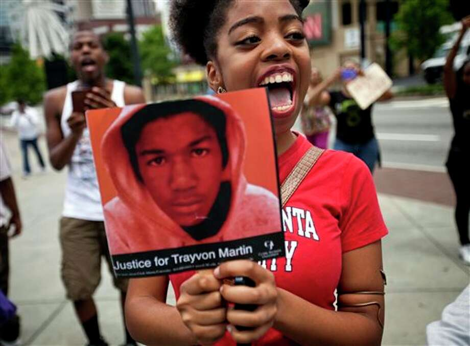 Averri Liggins, 22, of Atlanta, chants while holding a picture of Trayvon Martin during a protest the day after George Zimmerman was found not guilty in the 2012 shooting death of Martin, Sunday, July 14, 2013, in Atlanta. From New York to California, outrage over the acquittal of George Zimmerman poured from street demonstrations and church pulpits Sunday. (AP Photo/David Goldman) Photo: David Goldman / AP