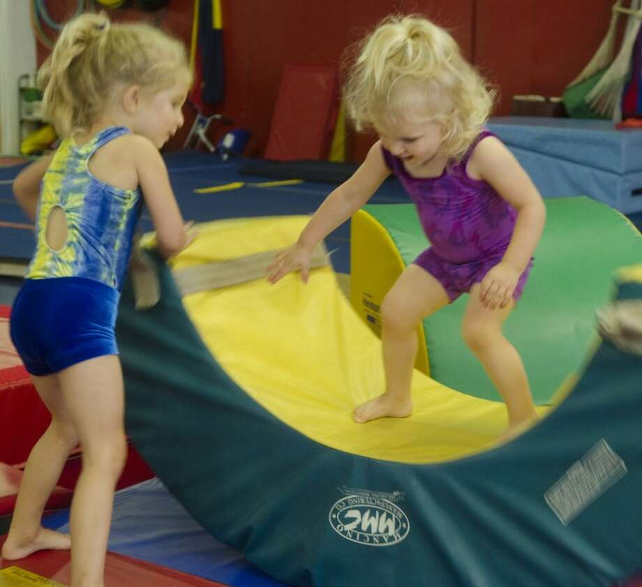 Audry Mann, 4, helps her sister, Scarlett, 2, on the balance mat Saturday during gymnastics practice at Next Level Gymnastics. Photo by Tim Fischer/Midland Reporter-Telegram Photo: Tim Fischer