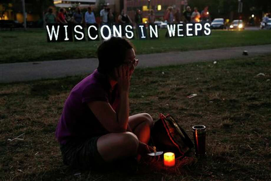 A woman sits with a candle during a vigil for the victims of the Sikh Temple of Wisconsin shooting, in Milwaukee, Sunday, Aug 5, 2012. An unidentified gunman killed six people at a Sikh temple in suburban Milwaukee in a rampage that left terrified congregants hiding in closets and others texting friends outside for help. The suspect was killed outside the temple in a shootout with police officers. (AP Photo/Jeffrey Phelps) Photo: JEFFREY PHELPS / AP2012